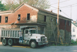 This image shows the stripping away of the asphalt siding sometimes referred to by its brand names such as Insulbrick or Insulstone, to reveal the original wood clapboard siding underneath.