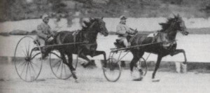 The trotter, Nancy Hanks, is shown on the right is hitched to a sulky fitted with pneumatic tires while the prompter horse on the left is shown hitched to the old wooden high-wheeled sulky. The smaller rubber inner-tube wheels produced faster times for a horse than the big wood wheels and the high-wheelers stopped being used in races by the late 1890s.